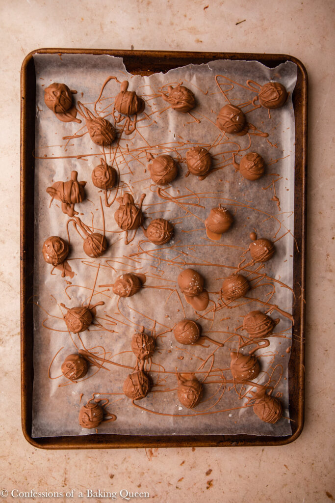 chocolate dipped truffles chilling on a baking sheet on a light brown surface