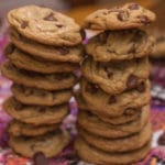 Perfect Chocolate Chip Cookies in two tall stacks on a flowery tea towel on a wood table