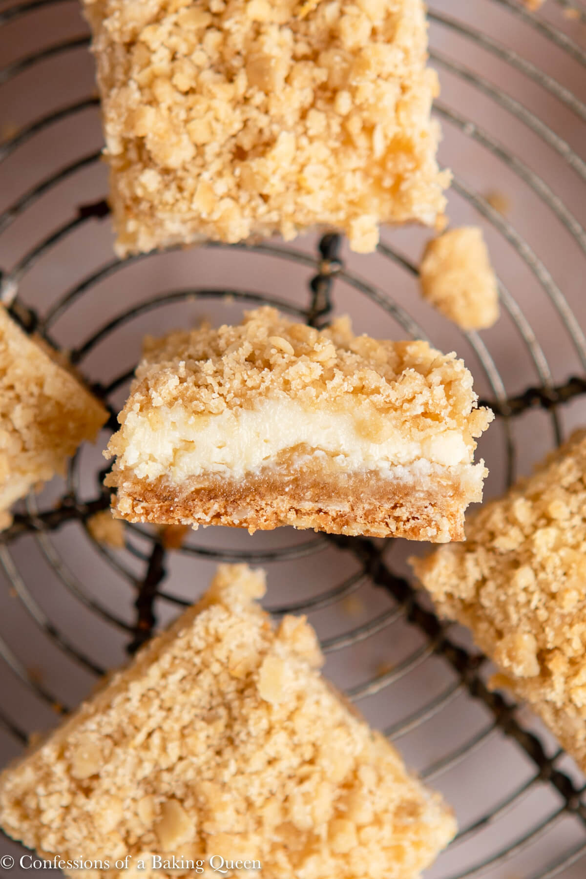 close up of lemon crumb bars on a wire rack on a light pink surface