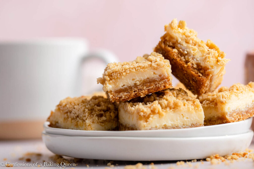 lemon crumble bars stacked on top of each other on a stack of white plates on a pink background with a cup of coffee in the background