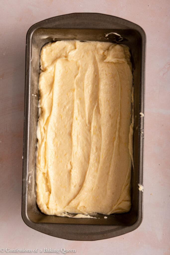 lemon loaf cake batter in a loaf pan before baking on a light pink surface