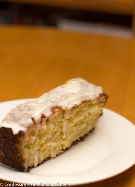 Lemon Loaf with Lemon Glaze slice on a white plate on a wood table