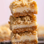 stack of creamy lemon crumb bars on a wire rack on a pink surface