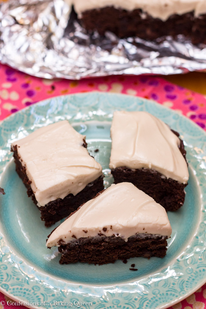 guinness brownies with baileys frosting on a blue plate on top of a pink tea towel