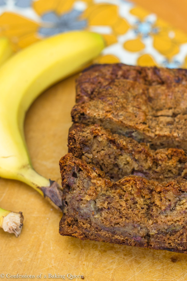cut slices of pudding banana bread on a wood board with a banana next to it all sitting on a yellow grey and white tea towel