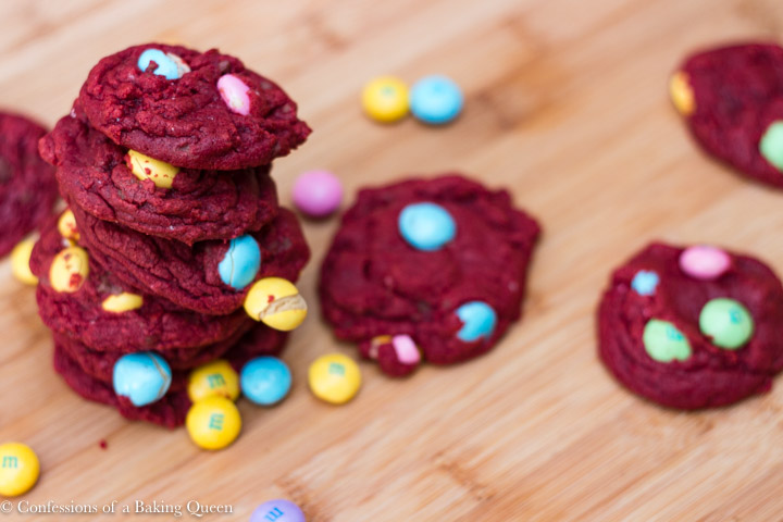 vertical image of red velvet m&m white chocolate cookies stacked high on a wood board