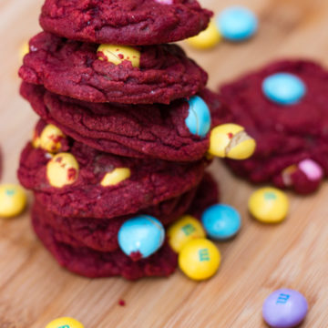 red velvet m&m white chocolate cookies stacked high on a wood board