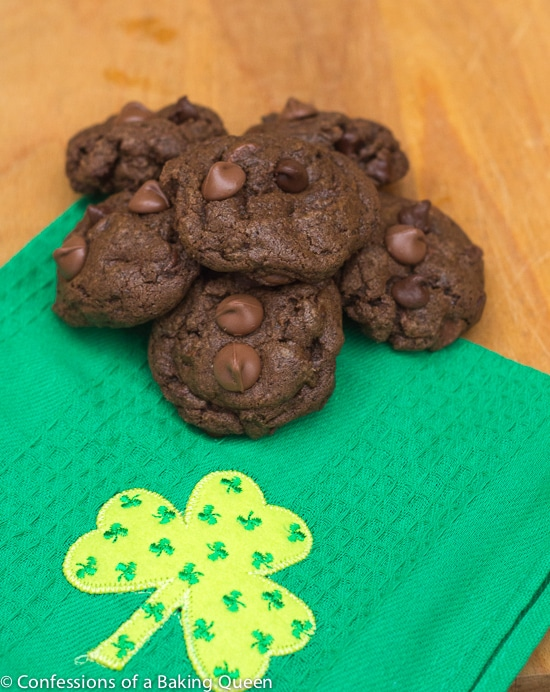 Triple Chocolate Thin Mint Cookies baked and stacked on a green towel on a wood board