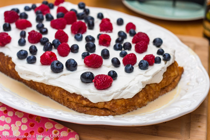 baileys tres leches cake with fresh berries on a white serving platter sitting on a wood board with a pink linen