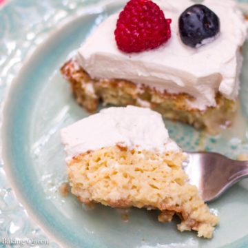 Bailey's Tres Leches Cake on a blue plate with a bite taken out on a pink linen