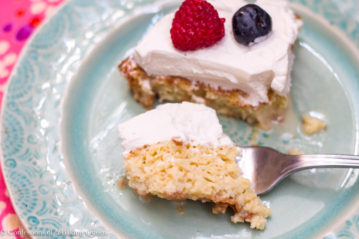 Bailey's Tres Leches Cake on a blue plate with a bite taken out sitting on a pink linen