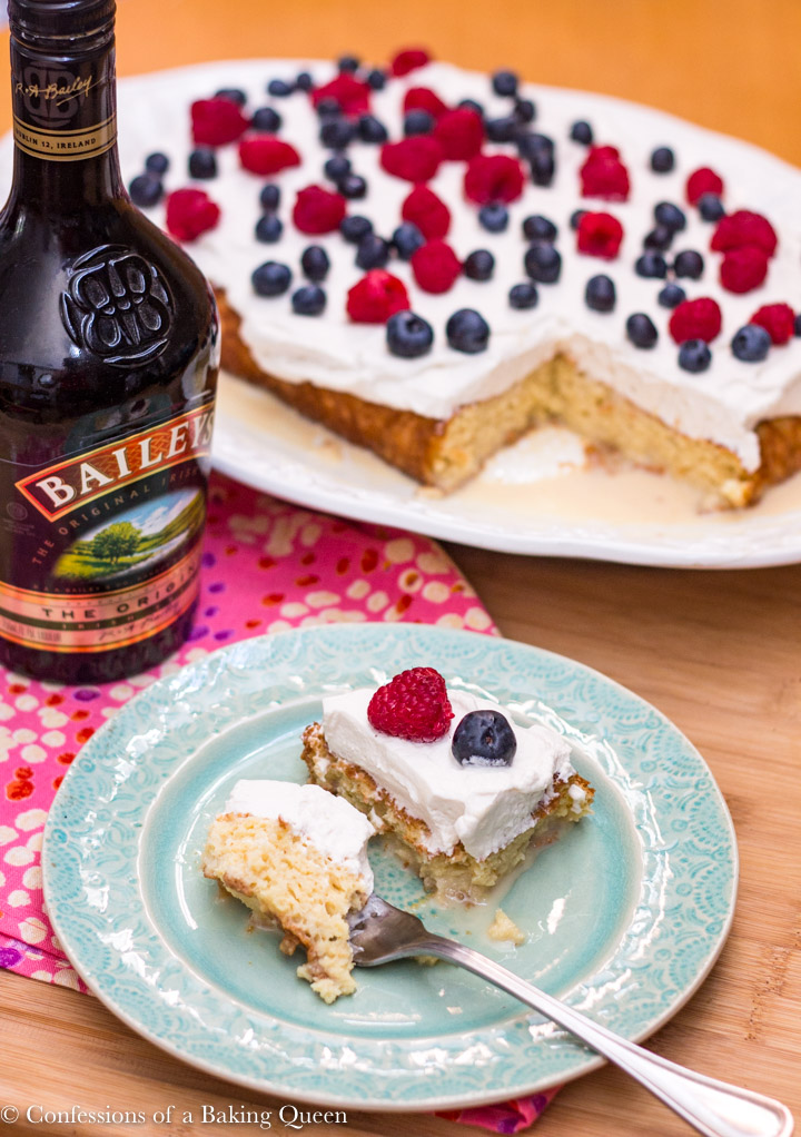 Bailey's Tres Leches Cake on a blue plate with a bite taken out with a bottle of baileys and the rest of the cake in the background