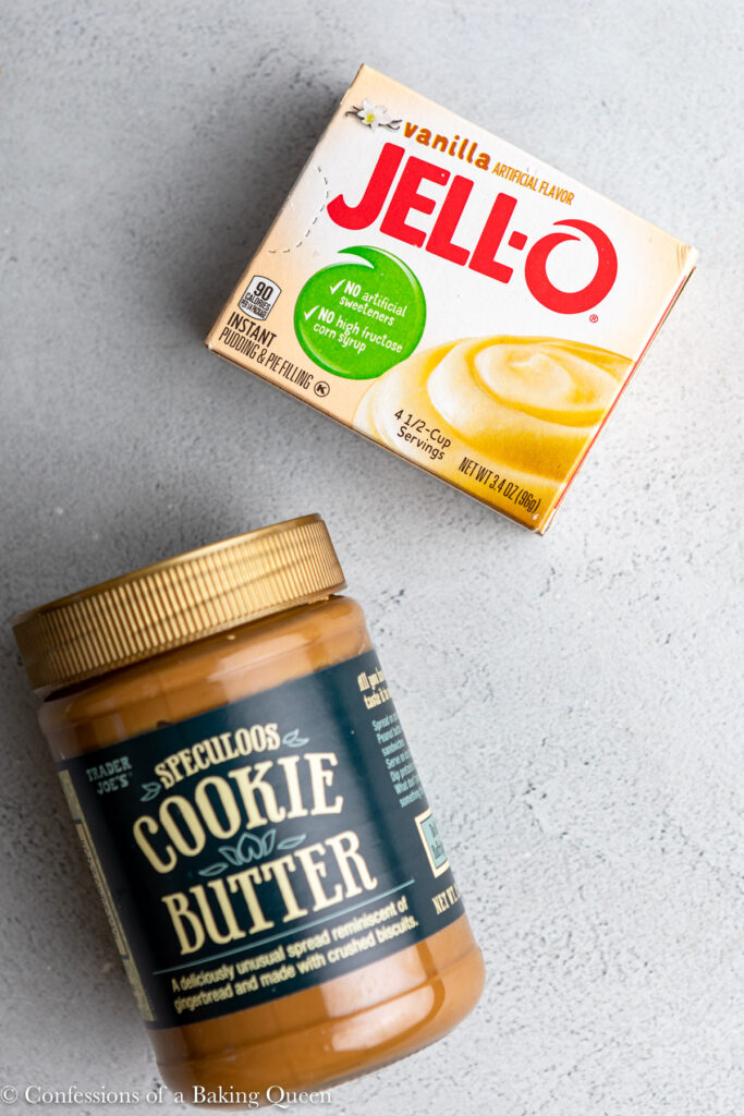 box of vanilla pudding mix and jar of cookie butter on a grey surface