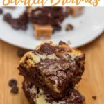 caramel cheesecake swirl brownies stacked on top of each other on a wood board