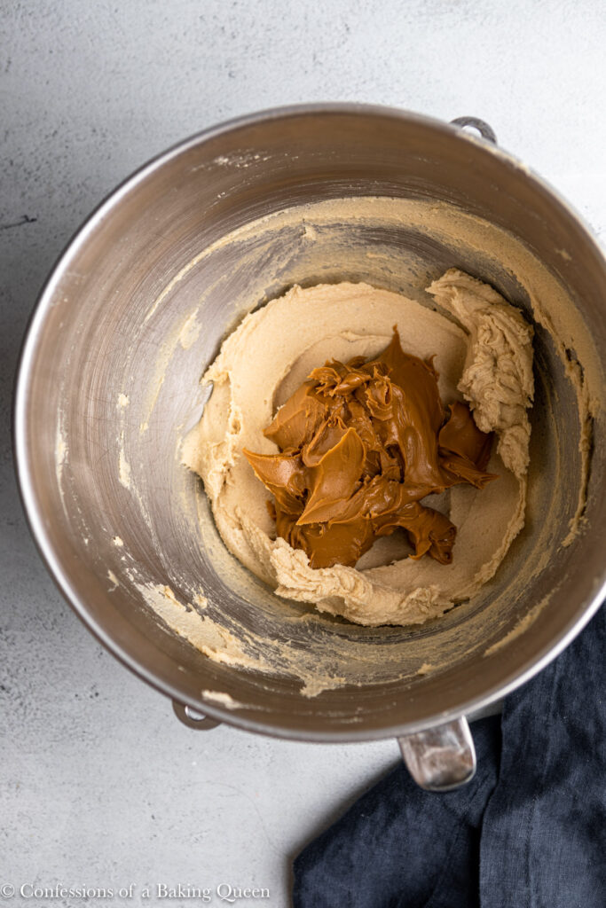 cookie butter added to creamed sugar mixture in a metal bowl on a grey surface with a navy blue linen