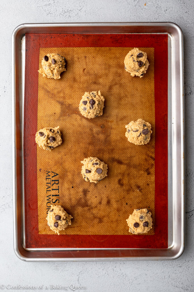 cookie butter chocolate chip cookies before baking on a silpat lined baking sheet on a grey surface