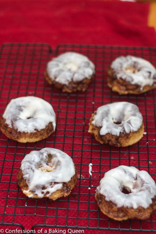 Apple Cinnamon Roll Doughnuts dunked in cream cheese frosting setting on a wire rack with red towel underneath