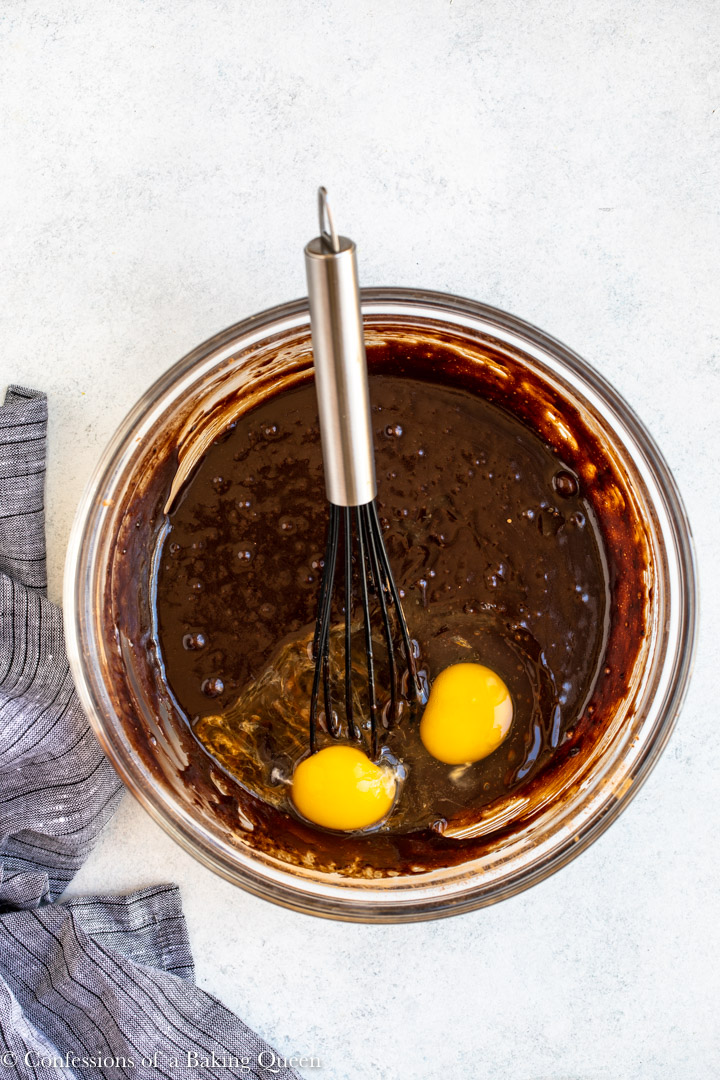 egg and egg yolk added to brownie batter in a glass bowl