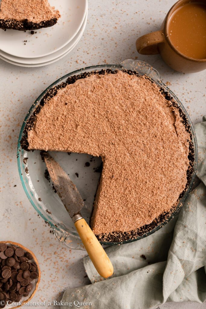 slices missing from baileys chocolate pie with a knife next to props on alight grey surface