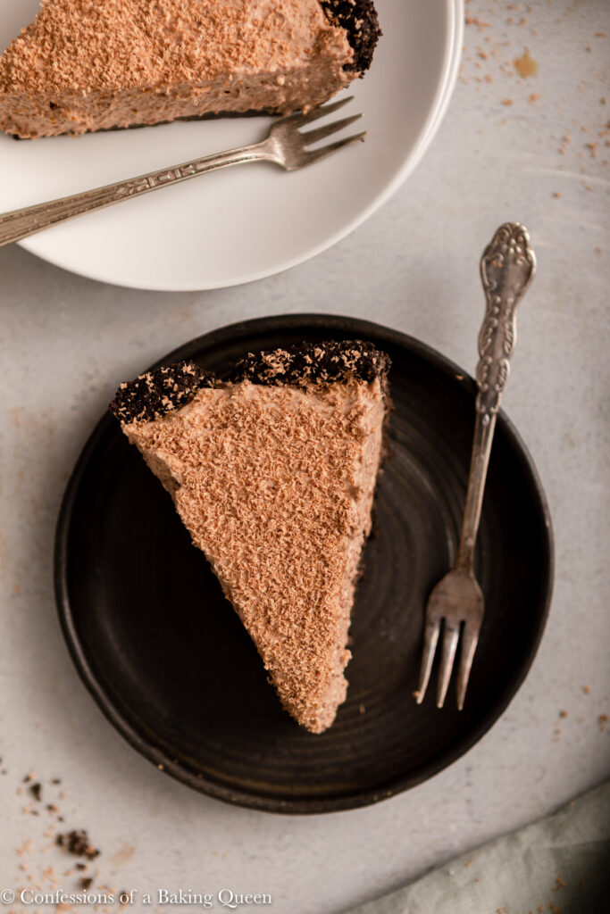 slices of baileys chocolate cream pie on black and white plates with forks on a light grey surface