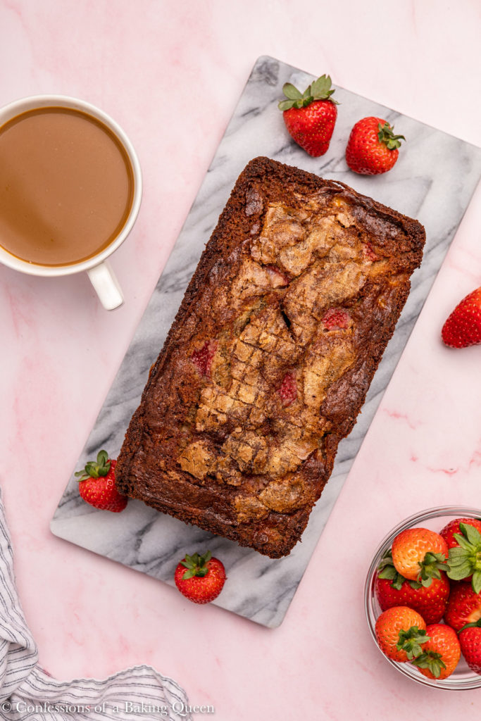 strawberry banana bread loaf on a marble platter with strawberries and a cup of coffee