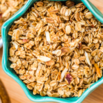homemade granola recipe in a turquoise bowl on a wood board