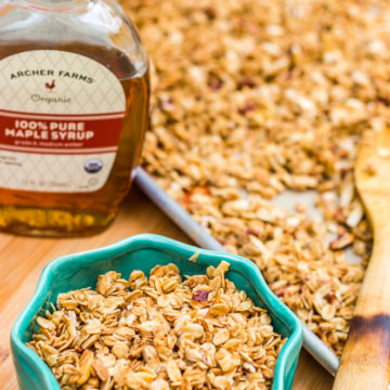homemade maple granola recipe on a baking sheet and in a turquoise bowl with a bottle of maple syrup all on a wood board