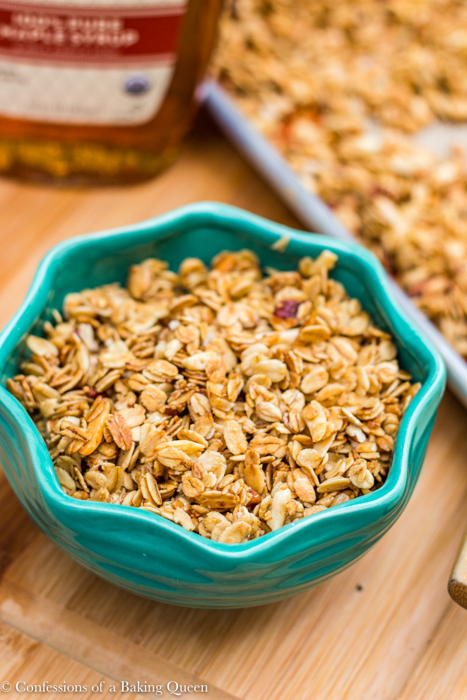 homemade maple granola in a turquoise bowl with a baking sheet with granola on in the background on a wood board