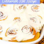 cinnamon rolls baked and frosted in a rectangle ceramic dish