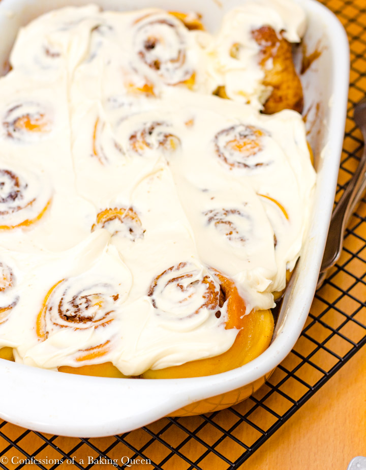 overnight cinnamon rolls in a ceramic dish on a black rack on a wood table