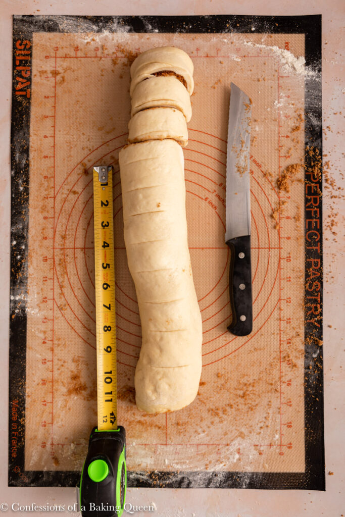 cinnamon roll log next to measuring tape and knife on a work surface on top of a light pink surface
