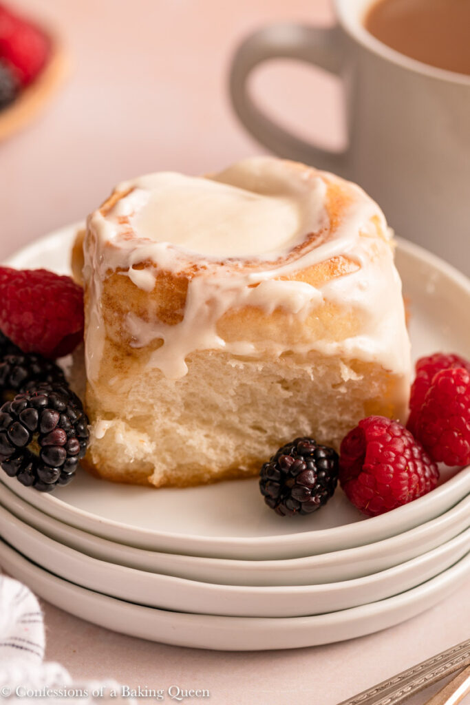 cinnamon roll on a stack of white plates with berries on a light pink surface with a cup of coffee and linen