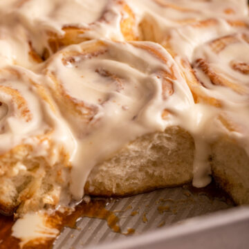 close up of cream cheese frosted cinnamon rolls in a pan