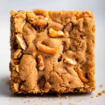close up of pretzel chocolate chip blondie on a grey surface