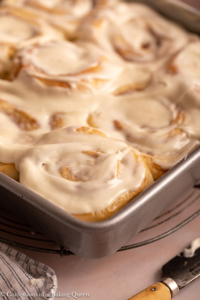 cream cheese frosted cinnamon rolls in a pan next to a knife and linen