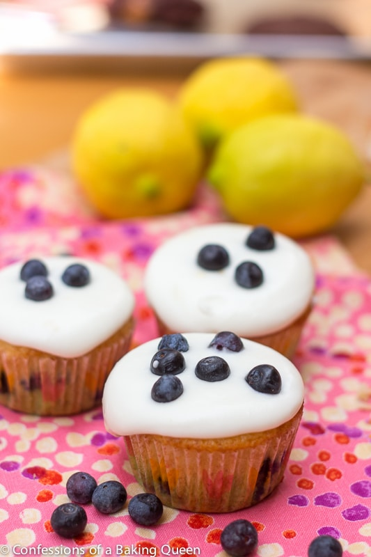 Lemon Blueberry Cupcakes sitting on a pink linen with blueberries and lemons in the background