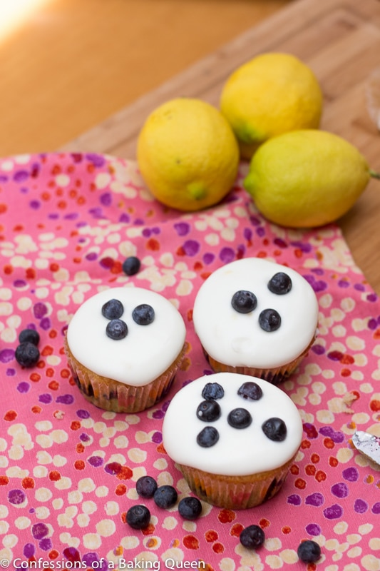 Lemon Blueberry Cupcakes on a pink linen with blueberries and lemons all on a wood board