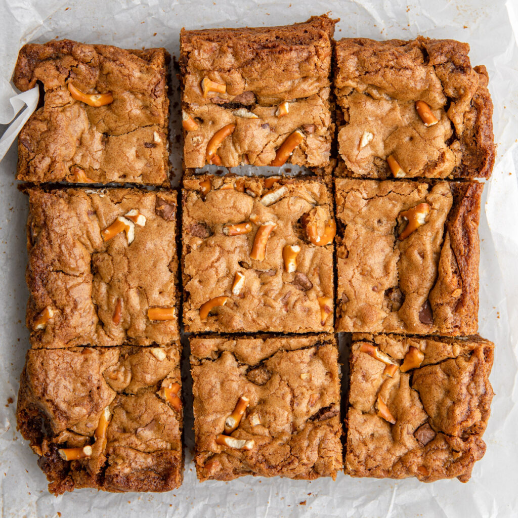 pretzel chocolate chunk blondies cut into squares on a parchment paper on a grey surface