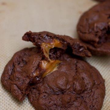 Double Chocolate Caramel Stuffed Cookie broken in half on a silpat lined baking sheet