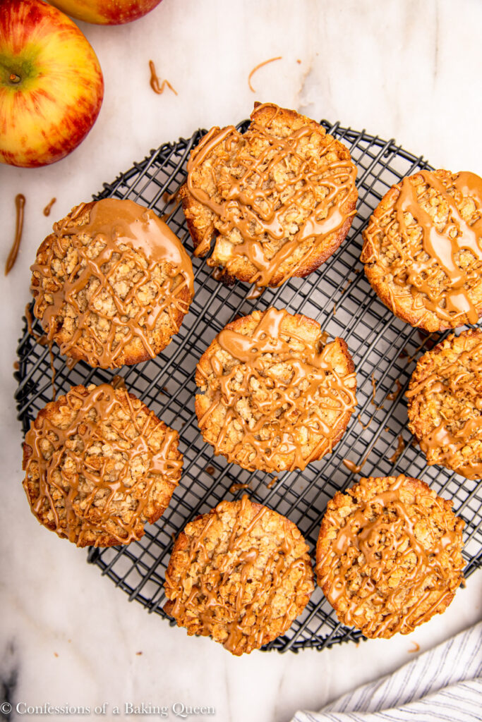 maple glazed apple muffins on a wire rack on a white marble surface