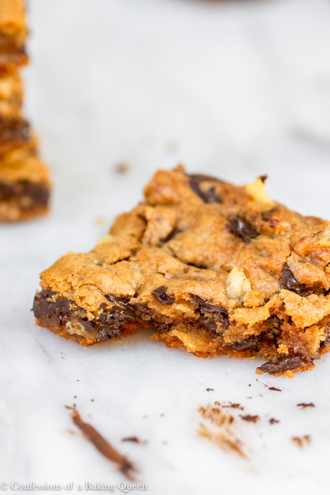 potato chip chocolate chunk blondie with a bite missing on a white marble surface