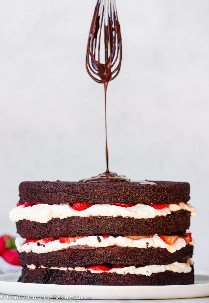 whisk with chocolate ganache dripping down on to a strawberries and cream chocolate cake