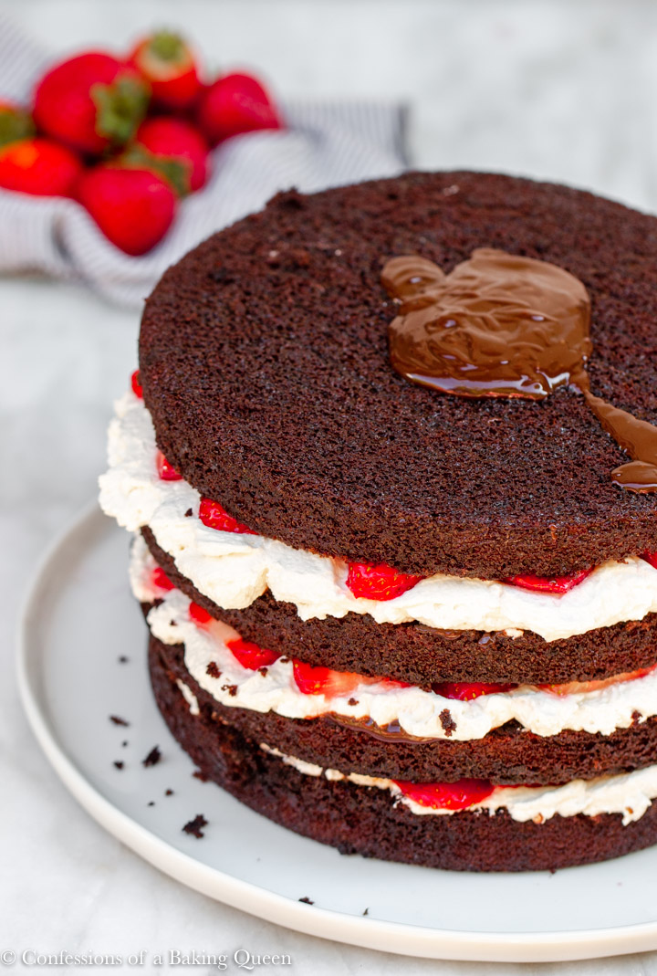 chocolate ganache poured on top of a strawberries and cream layer cake