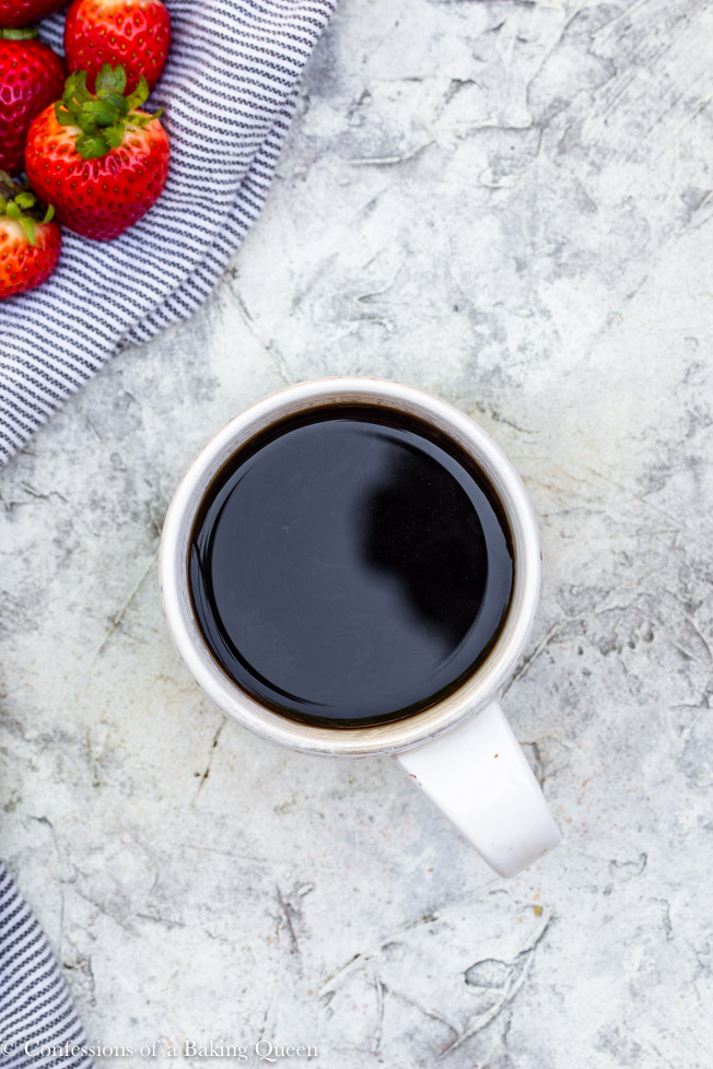 coffee cup on a grey background with strawberries on the side