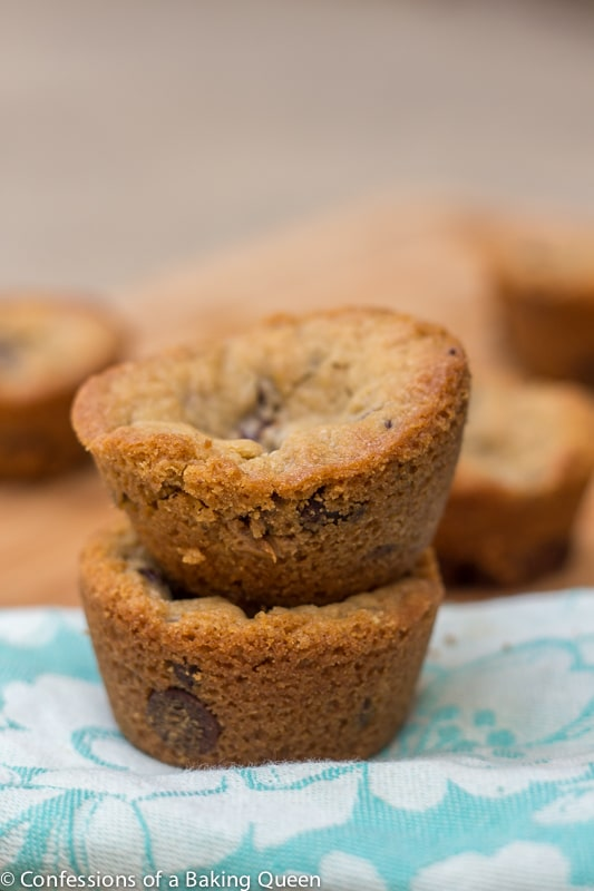 Truffle Stuffed Chocolate Chip Cookie Cups stacked on top of each other on a blue tea towel