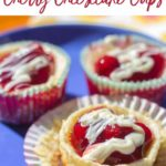 white chocolate drizzled cherry cheesecakes on a blue plate