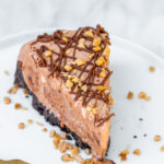 slice of a baileys double chocolate ice cream cake recipe on a white plate with gold fork