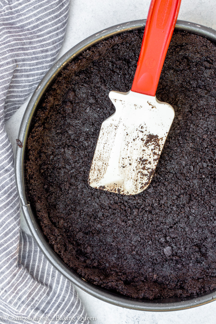 oreo cookie crust being pressed into a springform pan with a white spatula on a white surface with a blue linen
