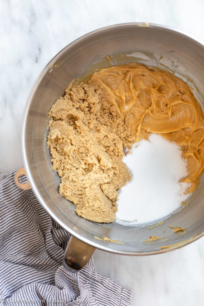 peanut butter and sugars in metal mixing bowl on a white marble surface with a white and blue linen