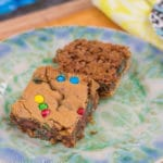 Pretzel Crusted M&M Blondies on an blue and green plate on a wood board with a yellow linen